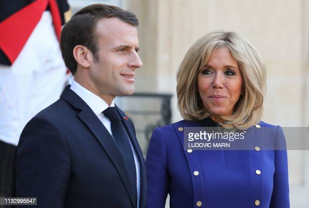 TOPSHOT French President Emmanuel Macron and his wife Brigitte Macron look on after accompanying back the Chinese president and his wife following a...