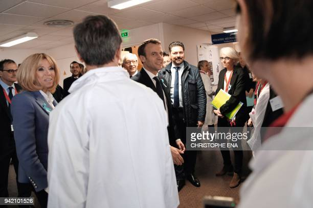 French President Emmanuel Macron and his wife Brigitte Macron meet hospital staff during a visit to the Rouen hospital Normandy on April 5 2018...