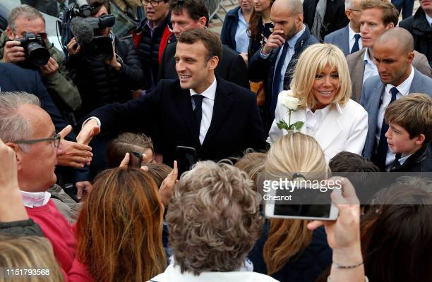 French President Emmanuel Macron and his wife Brigitte Macron pose for photos with supporters after casting their vote in the European elections on...