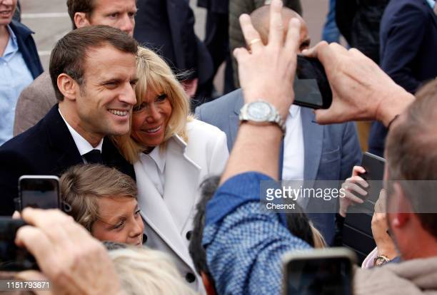 French President Emmanuel Macron and his wife Brigitte Macron pose for photos with supporters as they leave the polling station after casting their...