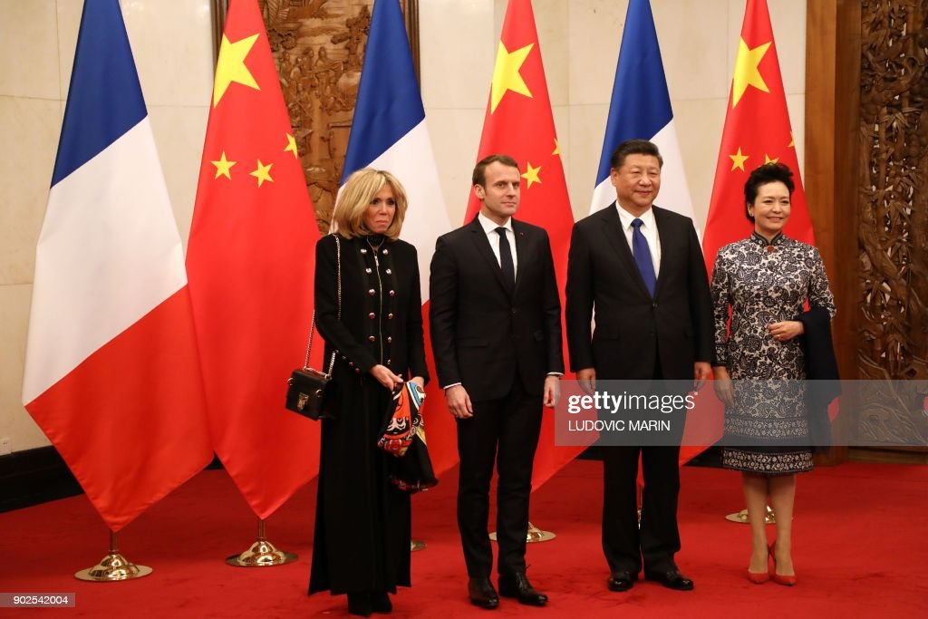 French President Emmanuel Macron (2nd L) and his wife Brigitte Macron (L) pose with Chinese President Xi Jinping (2nd R) and his wife Peng Liyuan at the Diaoyutai State Guesthouse in Beijing on January 8, 2018. French President Emmanuel Macron urged Europe on January 8 to take part in China's massive Silk Road infrastructure project but warned against 'hegemony', saying both sides should share the benefits. / AFP PHOTO / POOL / ludovic MARIN