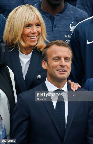 French President Emmanuel Macron and his wife Brigitte Macron pose with France's national football team players as they visit to the team's training...