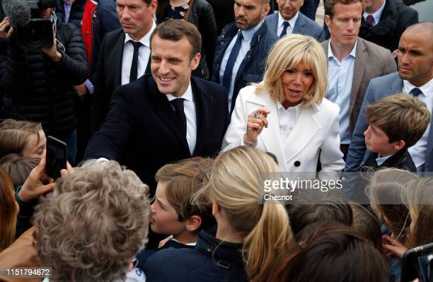 French President Emmanuel Macron and his wife Brigitte Macron shake hands with supporters as they leave the polling station after casting their vote...