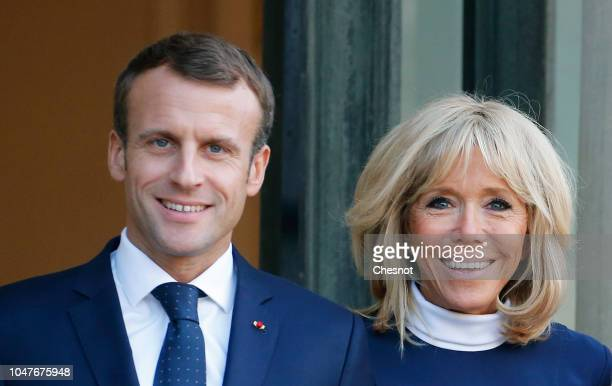 French President Emmanuel Macron and his wife Brigitte Macron stand outside the Elysee Presidential Palace to welcome Chilean President Sebastian...