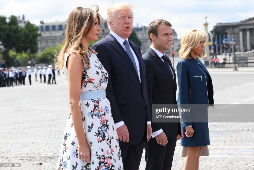 French President Emmanuel Macron (2nd R) and his wife Brigitte Macron (R) stand with US President Donald Trump and US First Lady Melania Trump after attending the annual Bastille Day military parade on the Champs-Elysees avenue in Paris on July 14, 2017. The parade on Paris's Champs-Elysees will commemorate the centenary of the US entering WWI and will feature horses, helicopters, planes and troops. /
