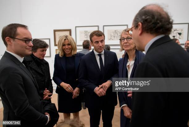 French President Emmanuel Macron and his wife Brigitte Macron talk with director of the Picasso museum Laurent Le Bon during the opening of the...