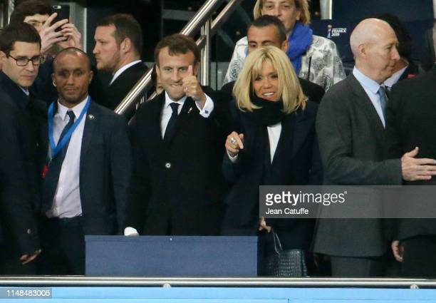 French President Emmanuel Macron and his wife Brigitte Macron congratulate the players of team France standing above them following the 2019 FIFA...