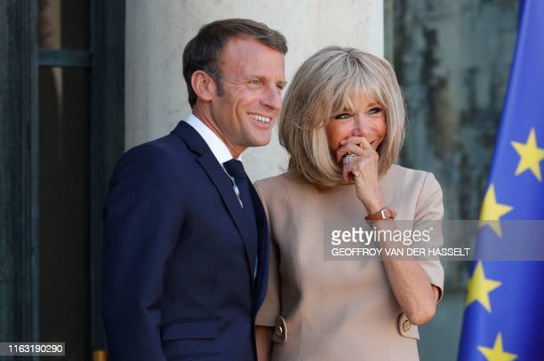 French President Emmanuel Macron and his wife Brigitte Macron wait for the arrival of the Greek Prime Minister prior to a meeting at the Elysee...