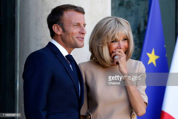 French President Emmanuel Macron and his wife Brigitte Macron wait for Greek Prime Minister Kyriakos Mitsotakis prior to their meeting at the Elysee...