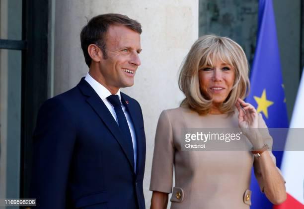 French President Emmanuel Macron and his wife Brigitte Macron wait for Greek Prime Minister Kyriakos Mitsotakis prior to their meeting at the Elysee...
