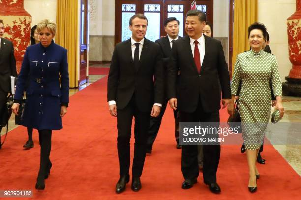 French President Emmanuel Macron and his wife Brigitte Macron walk with Chinese President Xi Jinping and Xi's wife Peng Liyuan during their meeting...