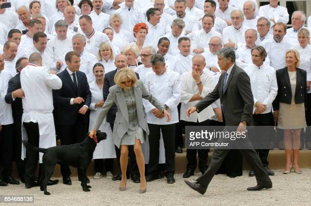 French President Emmanuel Macron and his wife Brigitte Macron walking their dog Nemo pose for a photograph with French chefs during an event at the...