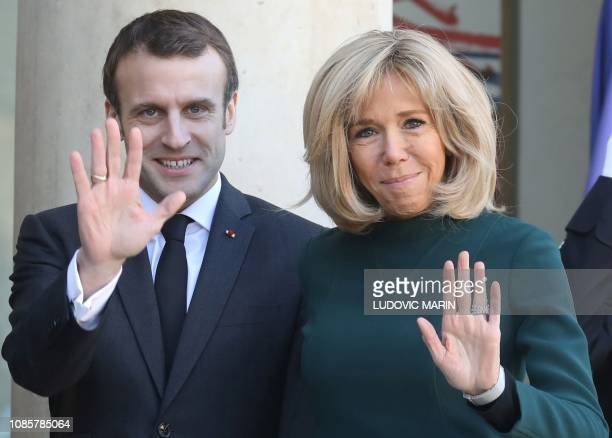 TOPSHOT French President Emmanuel Macron and his wife Brigitte Macron wave as they wait for the arrival of Quebec's Prime Minister at the Elysee...