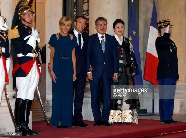 French President Emmanuel Macron and his wife Brigitte Macron welcome South Korean President Moon Jae-in and his wife Kim Jung-sook prior to a state...
