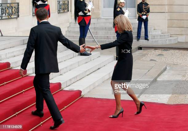French President Emmanuel Macron and his wife Brigitte Macron welcome former French President Francois Hollande prior to a lunch at the Elysee...