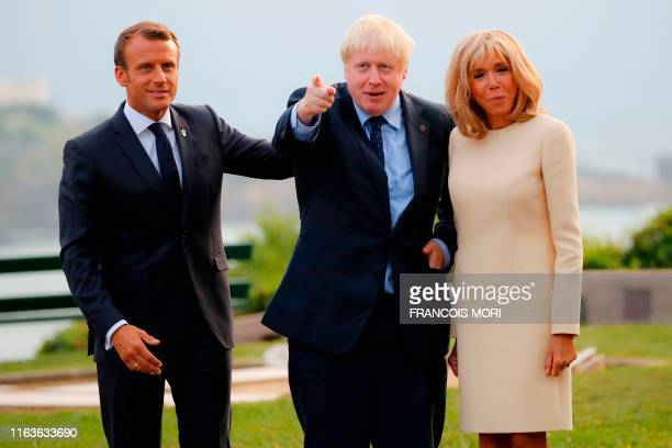 TOPSHOT French President Emmanuel Macron and his wife Brigitte welcome Britain's Prime Minister Boris Johnson at the Biarritz lighthouse southwestern...