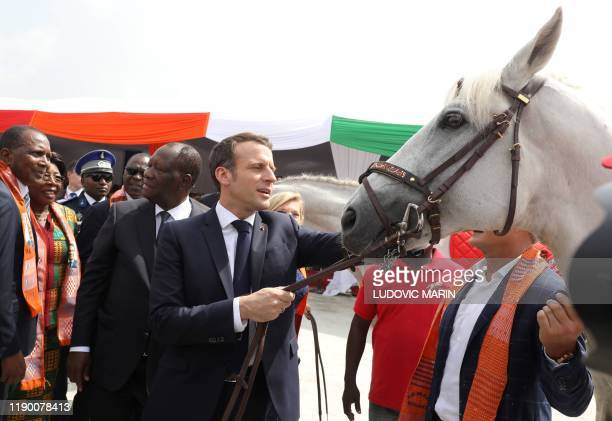 French President Emmanuel Macron and Ivorian President Alassane Ouattara receive as presents two horses from local officials during a ceremony to lay...