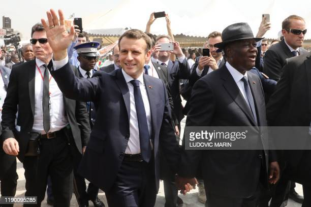 French President Emmanuel Macron and Ivorian President Alassane Ouattara arrive to attend a ceremony to lay the first brick of the future Bouake...