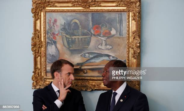 French President Emmanuel Macron and Ivory Coast President Alassane Ouattara attend a ceremony at the Presidential Palace in Abidjan on November 30...