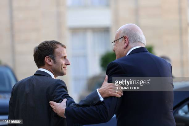 French President Emmanuel Macron and Lebanese Prime Minister Najib Mikati walk after a working lunch at the Elysee Palace, in Paris, on September 24,...