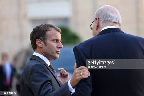 French President Emmanuel Macron and Lebanese Prime Minister Najib Mikati talk after a working lunch at the Elysee Palace, in Paris, on September 24,...
