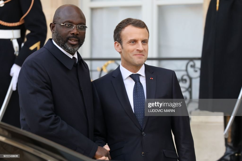 French President Emmanuel Macron (R) and Liberian President George Weah shake hands as they leave the Elysee presidential palace after a lunch on February 21, 2018 in Paris. /