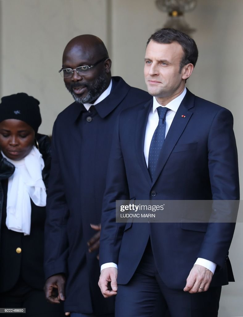 French President Emmanuel Macron (R) and Liberian President George Weah leave the Elysee presidential palace after a lunch on February 21, 2018 in Paris