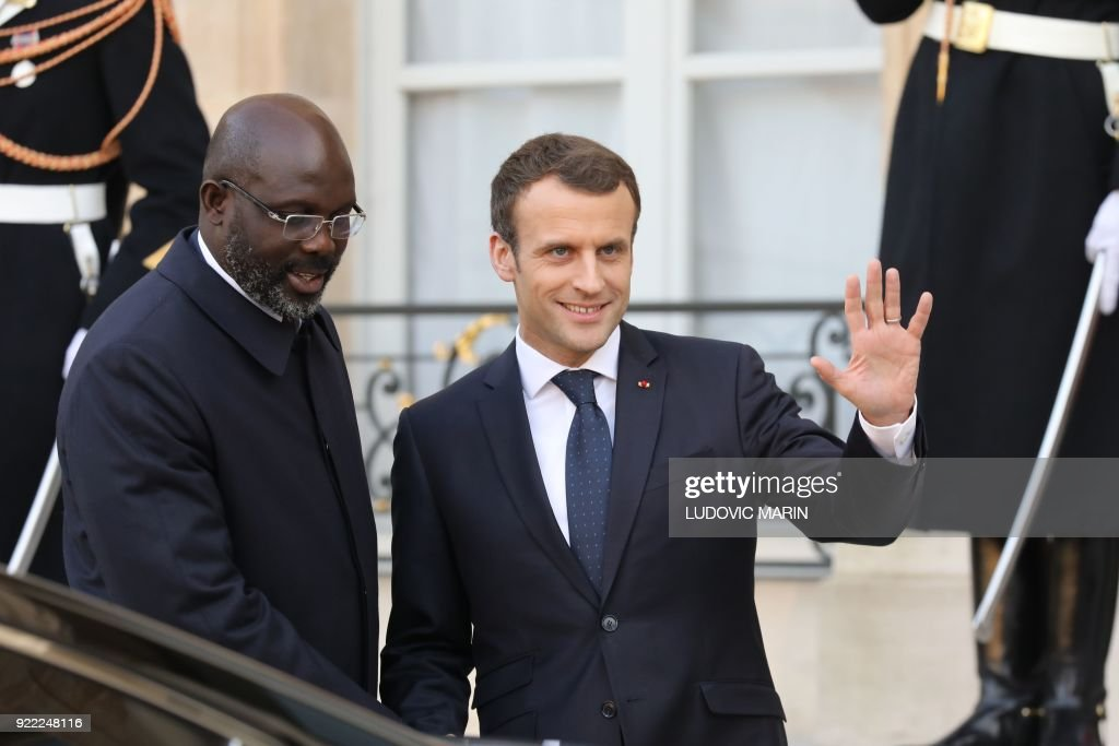 French President Emmanuel Macron (R) and Liberian President George Weah leave the Elysee presidential palace after a lunch on February 21, 2018 in Paris. /