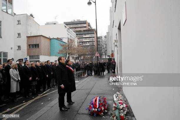 French President Emmanuel Macron and Paris mayor Anne Hidalgo observe a minute of silence outside the satirical newspaper Charlie Hebdo former office...