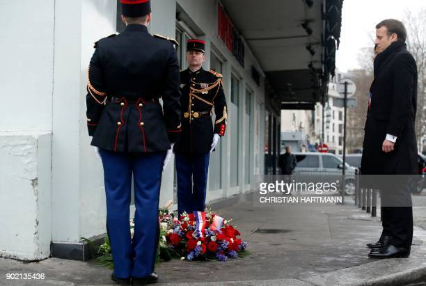 French President Emmanuel Macron and Paris mayor Anne Hidalgo pay their respect during a memorial ceremony outside the Hyper Casher supermarket to...