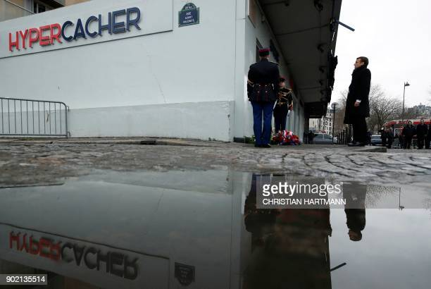 TOPSHOT French President Emmanuel Macron and Paris mayor Anne Hidalgo pay their respect during a memorial ceremony outside the Hyper Casher...