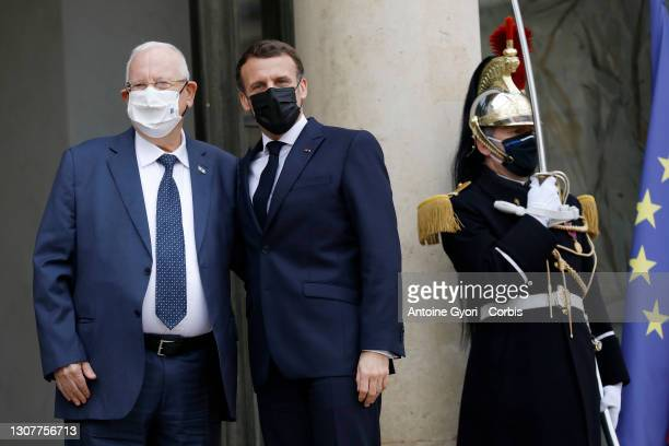 French President Emmanuel Macron and President of Israel Reuven Rivlin wearing protective face masks wave prior to their meeting at the Elysee...