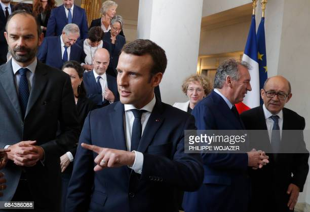French President Emmanuel Macron and Prime Minister Edouard Philippe leave after posing for a family photo after the first cabinet meeting at the...