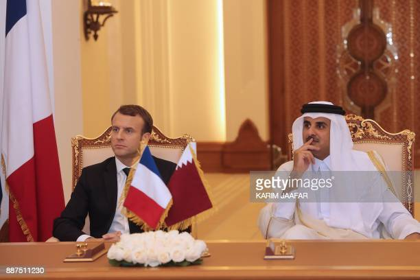 French President Emmanuel Macron and Qatari Emir Sheikh Tamim bin Hamad alThani watch as their foreign ministers sign bilateral agreements in the...