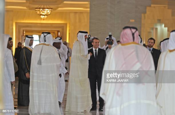 French President Emmanuel Macron and Qatari Emir Sheikh Tamim bin Hamad alThani are surrounded by Qatari officials during the reception of the French...