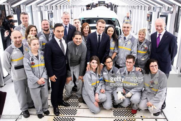 French President Emmanuel Macron and Renault CEO Carlos Ghosn pose with employees of the Renault factory after a visit in Maubeuge northeastern...