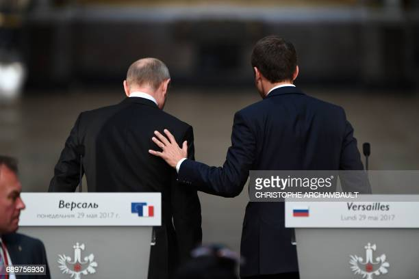 French President Emmanuel Macron and Russian President Vladimir Putin leave after delivering a joint press conference following their meeting at the...