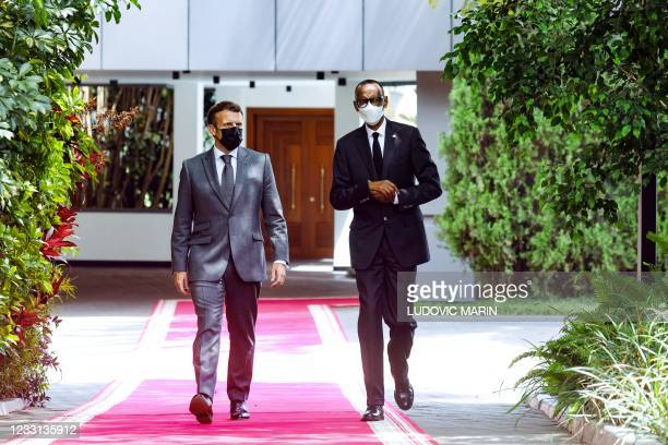 French President Emmanuel Macron and Rwanda's President Paul Kagame walk to hold a joint press conference at the Presidential Palace in Kigali on May...