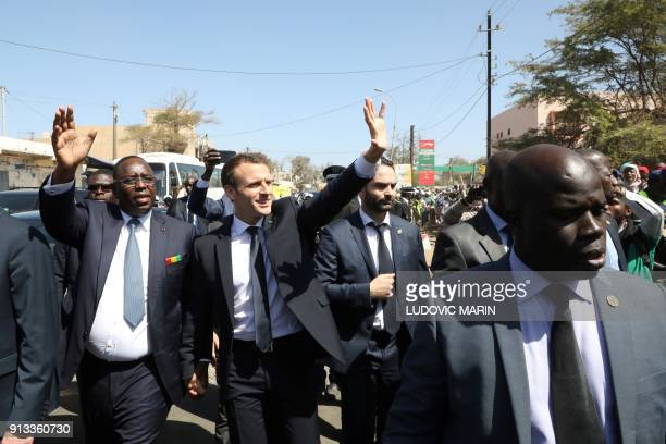 French President Emmanuel Macron and Senegalese President Macky Sall wave as they are greeted by a crowd and students during a visit to inaugurate...