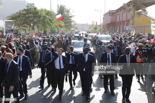 French President Emmanuel Macron and Senegalese President Macky Sall wave at the crowd as they walk in Saint-Louis on February 3 on the final day of...