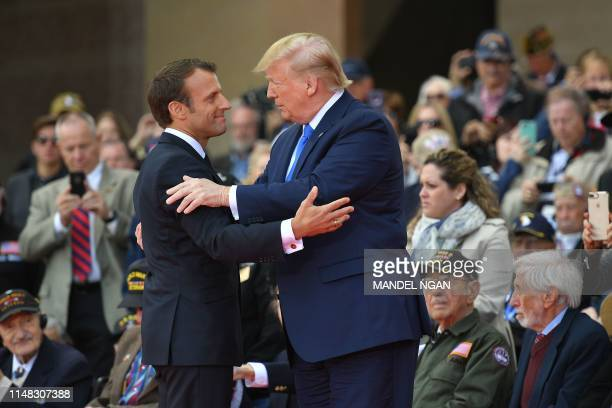 French President Emmanuel Macron and US President Donald Trump embrace during a FrenchUS ceremony at the Normandy American Cemetery and Memorial in...