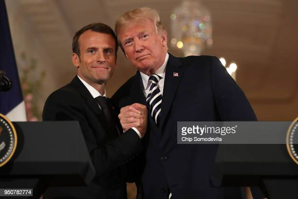 French President Emmanuel Macron and US President Donald Trump embrace at the completion of a joint press conference in the East Room of the White...