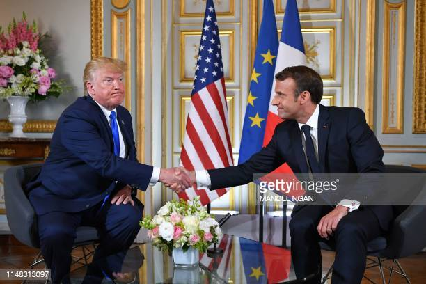 TOPSHOT French President Emmanuel Macron and US President Donald Trump shake hands during a meeting at the Prefecture of Caen Normandy northwestern...
