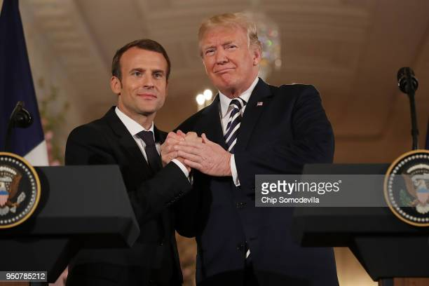 French President Emmanuel Macron and US President Donald Trump shake hands at the completion of a joint press conference in the East Room of the...