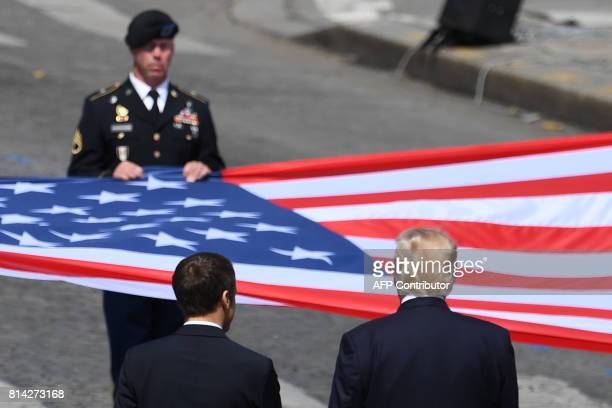 French President Emmanuel Macron and US President Donald Trump stand in front of the US national flag held by soldiers at the end of the annual...