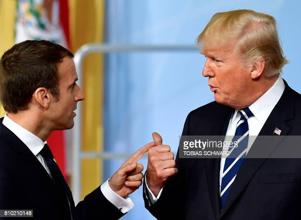 French President Emmanuel Macron and US President Donald Trump talk after a family photo of the participants of the G20 summit in Hamburg northern...