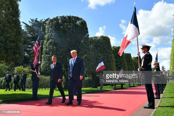 TOPSHOT French President Emmanuel Macron and US President Donald Trump walk on the red carpet during a FrenchUS ceremony at the Normandy American...