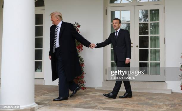 TOPSHOT French President Emmanuel Macron and US President Donald Trump walk to the Oval Office prior to a meeting at the White House in Washington DC...
