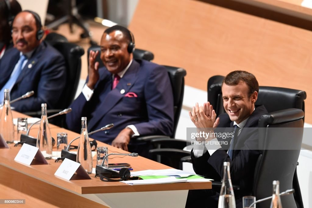 French President Emmanuel Macron (R) applauds a question posed by a student, as President of the Republic of Congo Denis Sassou-Nguesso (C) smiles, at the One Planet Summit on December 12, 2017, at La Seine Musicale venue on l'ile Seguin in Boulogne-Billancourt, west of Paris. The French President hosts 50 world leaders for the 'One Planet Summit', hoping to jump-start the transition to a greener economy two years after the historic Paris agreement to limit climate change. / AFP PHOTO / Eric FEFERBERG