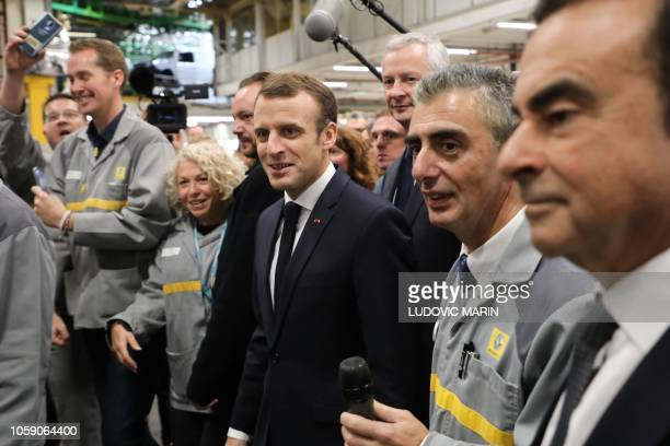 French President Emmanuel Macron arrives flanked by Chairman and CEO of RenaultNissanMitsubishi Carlos Ghosn and followed by French Economy Minister...